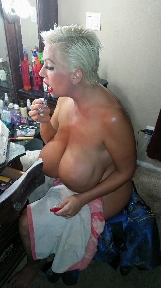 Big boobs putting on lipstick